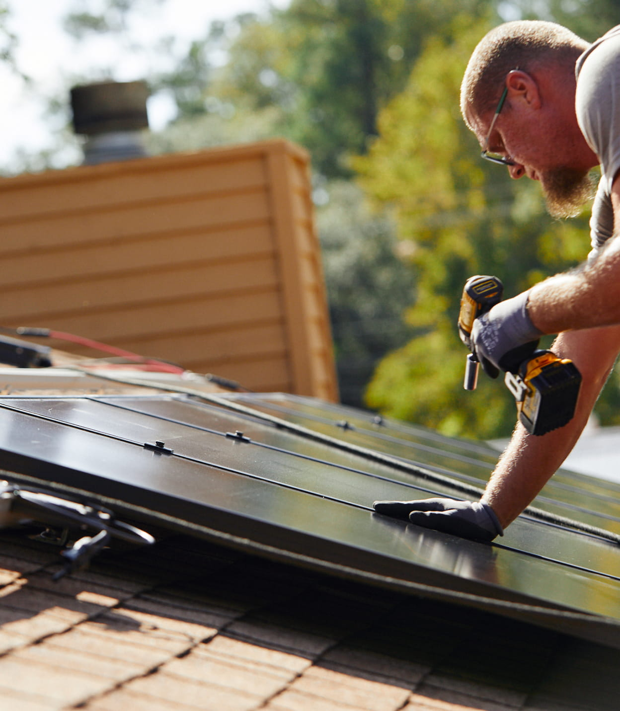 person installing solar panels on roof