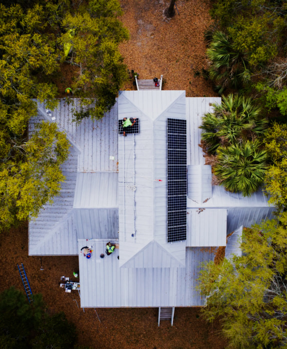 Overhead drone shot of a Palmetto solar power system being installed on a roof